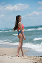 Slim girl wear bikini, beach with wild waves Royalty Free Stock Photo