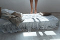 Slim legs of young woman flying in air above bed Royalty Free Stock Photo