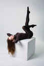 Slim female long legs in black pantyhose on studio box. Royalty Free Stock Photo