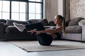 Slim sporty girl doing v-ups abs workout at home Royalty Free Stock Photo