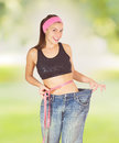 Slim waist slimming body successful diet of young woman with perfect healthy thin showing her old jeans after over nature Stock Image