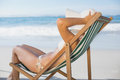 Slim woman relaxing in deck chair on the beach a sunny day Stock Photos