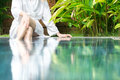 Slim woman white bathrobe sitting pool hotel her feet blue clear water fresh natural atmosphere green plants around hotels resorts Royalty Free Stock Image