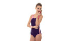 Slim young girl in a beautiful body swimsuit stands up straight and keeps a hand near the face Royalty Free Stock Photo