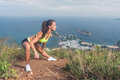 Slim young woman doing side lunge stretching exercise on top of the mountain with sea and sky in background