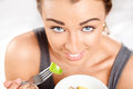 Slim young woman eating fruit salad Stock Photos