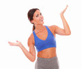 Slim young woman raising both palms with vitality in sport clothing against white background copyspace Stock Photos