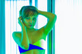 Slim young woman standing in solarium getting sun tan Royalty Free Stock Photo