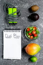 Slimming. Notebook for diet plan, fruits and salad and skipping rope on grey stone table top view mock up