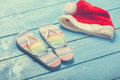 Slippers and christmas hat beach on blue wood Royalty Free Stock Photography