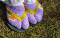 Slippers with color sock close up woman legs in on green grass natural winter Royalty Free Stock Photography