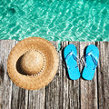 Slippers at jetty and hat by the sea Royalty Free Stock Images