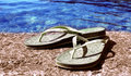 Slippers at the sea coast Royalty Free Stock Photo