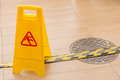 Slippery icon on yellow plastic warning sign alerts for hazard o Royalty Free Stock Photo