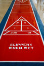 Slippery when wet a red and blue shuffleboard court with rain with warning Royalty Free Stock Photography