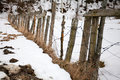 Slope of an old fence in the snow in the winter clear day Royalty Free Stock Photo