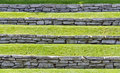 Slope reinforcement by natural stone walls hillside covered with grass and reinforced Royalty Free Stock Photo