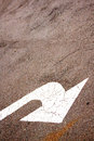 Sloping white painted arrow on asphalt road surface indicating right turn Royalty Free Stock Photos