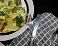stock image of  Close up on half of a plate with broccoli omelette and cutlery on the side