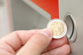 Slot machine hand holding a two euro coin infront of a focus is on the coin Stock Image