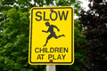Slow children at play sign yellow road Royalty Free Stock Image