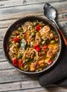 Slow cooker chicken with olives and sweet peppers in the pan on wooden background, top view. Royalty Free Stock Photo