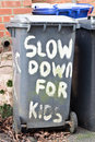 Slow down for kids written on a black bin Stock Photos