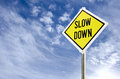 Slow down road sign yellow on blue sky with clouds background Royalty Free Stock Images