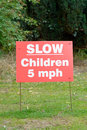 Slow down to miles per hour sign children present in park Royalty Free Stock Image