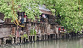 Slum on dirty canal in bangkok thailand Stock Photo