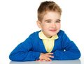 Sly little boy in blue cardigan and yellow shirt Royalty Free Stock Photos