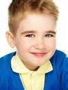 Sly little boy in blue cardigan and yellow shirt Royalty Free Stock Images