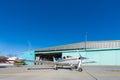 Small aeroplane standing before aircraft hangar at blue sky Stock Photography