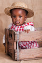 A small african girl dressed as a farm girl in a cradle Royalty Free Stock Photos