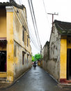 Small alley with the ancient house in hoi an man driving motorcycle on vietnam Royalty Free Stock Photography