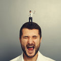 Small angry boss standing on the head and screaming at worker over grey background Royalty Free Stock Photography