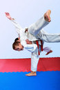Small athlete with a white belt performs throw judo Stock Images