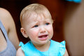 Small baby crying is hard tears stream down her cheeks Stock Photos