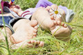 Small baby feet on grass two pairs of children s with daisy flower Royalty Free Stock Photos