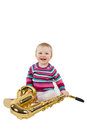 Small baby girl, playing with musical instrument, saxophone, iso Royalty Free Stock Photography