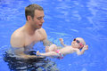 Small baby girl is swimming in the pool with daddy for first time three months old Royalty Free Stock Photos
