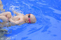 Small baby girl is swimming in the pool with daddy for first time three months old Royalty Free Stock Image