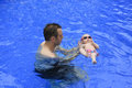 Small baby girl is swimming in the pool with daddy for first time three months old Stock Photo