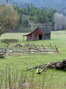 Small barn in pasture a weathered by a footbridge a field near coeur d alene idaho Royalty Free Stock Photo