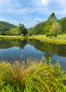 Small barn and trees frame summer pond Royalty Free Stock Photo