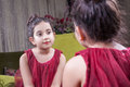 Small beautiful arab middle eastern girl with pretty red dress and lips posing and looking at herself in mirror years Royalty Free Stock Photos