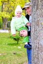 Small beautiful girl in green suit with father on glade Stock Photography