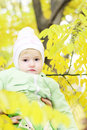 Small beautiful girl in green suit under yellow sheet on glade autumn Stock Photos