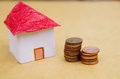 Small beautiful house with coins stacked in front of the housing model pretending: house prices, house buying, real Royalty Free Stock Photo