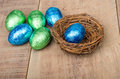Small bird's nest with green and blue foil eggs Royalty Free Stock Photos
